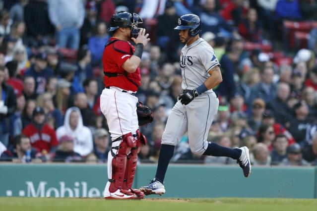 Tampa Bay Rays' Tommy Pham, right, scores in front of Boston Red Sox's Christian Vazquez on a single by Mike Zunino during the fourth inning of a baseball game in Boston, Saturday, April 27, 2019. (AP Photo/Michael Dwyer)