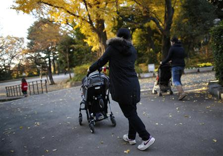 Filipino nannies stroll with children during their duty hours at a park in Tokyo