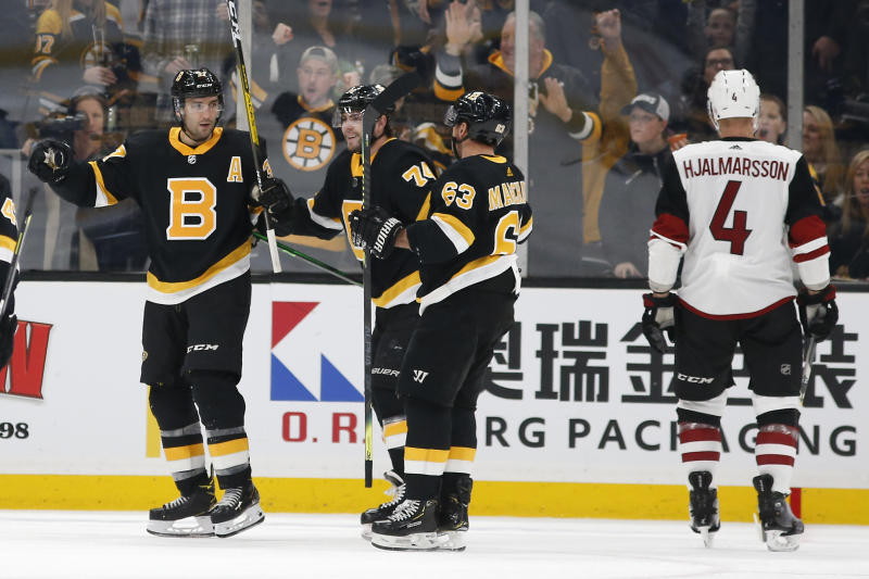 Boston Bruins' Patrice Bergeron, left, celebrates his goal with teammates Brad Marchand (63) and Jake DeBrusk as Arizona Coyotes' Niklas Hjalmarsson (4) skates away during the second period of an NHL hockey game Saturday, Feb. 8, 2020, in Boston. (AP Photo/Winslow Townson)