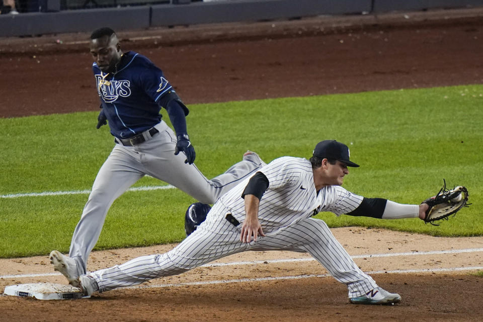 New York Yankees Mike Ford, right, stretches to make the catch for the out as Tampa Bay Rays' Randy Arozarena runs to first base during the sixth inning of a baseball game Tuesday, June 1, 2021, in New York. (AP Photo/Frank Franklin II)