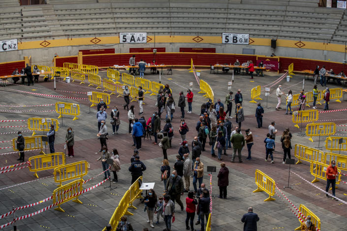 People queue to cast their votes during the regional election at the bullring in Moralzarzal, Spain, Tuesday, May 4, 2021. Over 5 million Madrid residents are voting for a new regional assembly in an election that tests the depths of resistance to lockdown measures and the divide between left and right-wing parties. (AP Photo/Manu Fernandez)