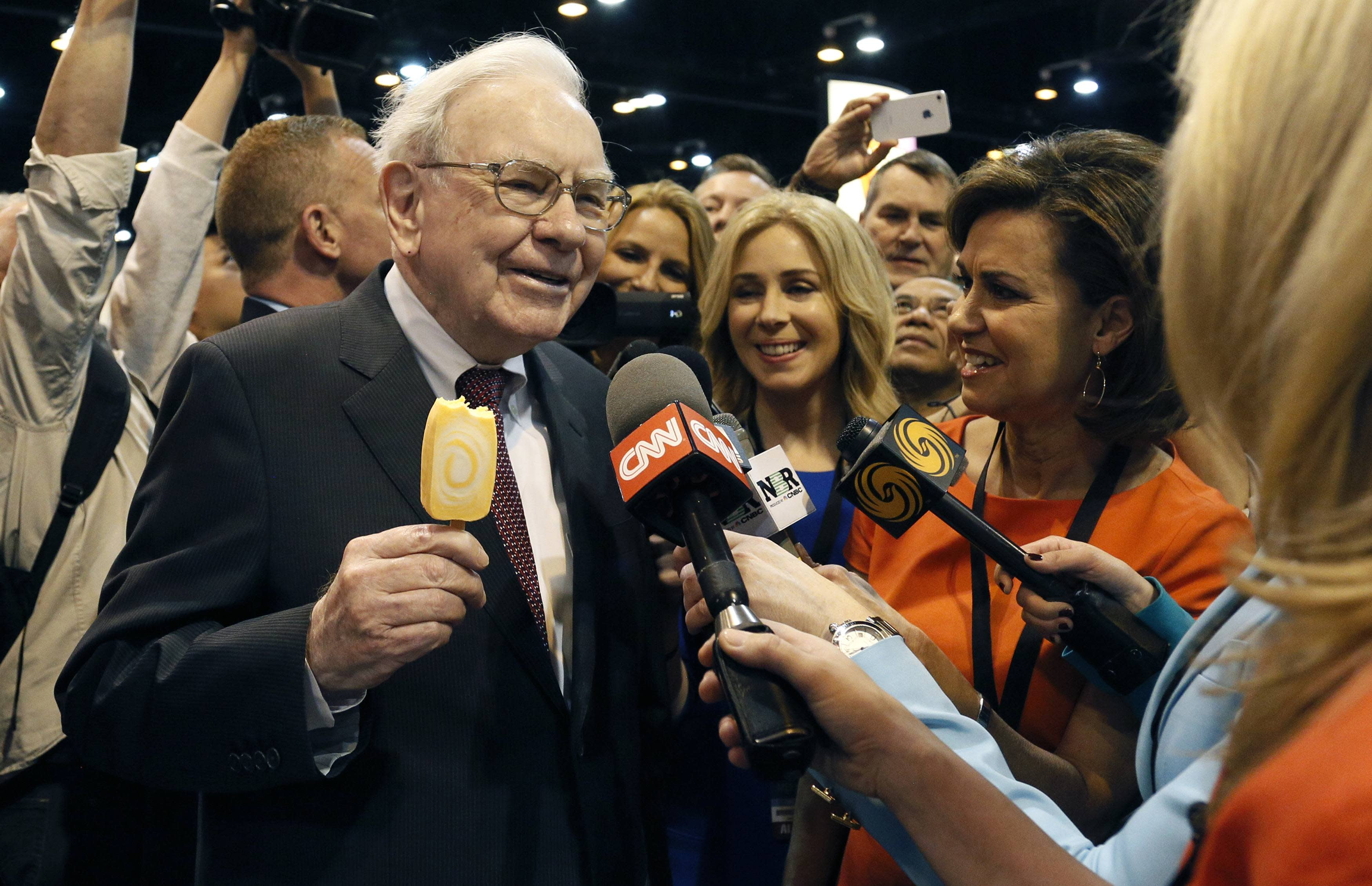Berkshire Hathaway CEO Warren Buffett talks to reporters while holding an ice cream at a trade show during the company's annual meeting in Omaha, Nebraska May 3, 2014. (Reuters/Rick Wilking)