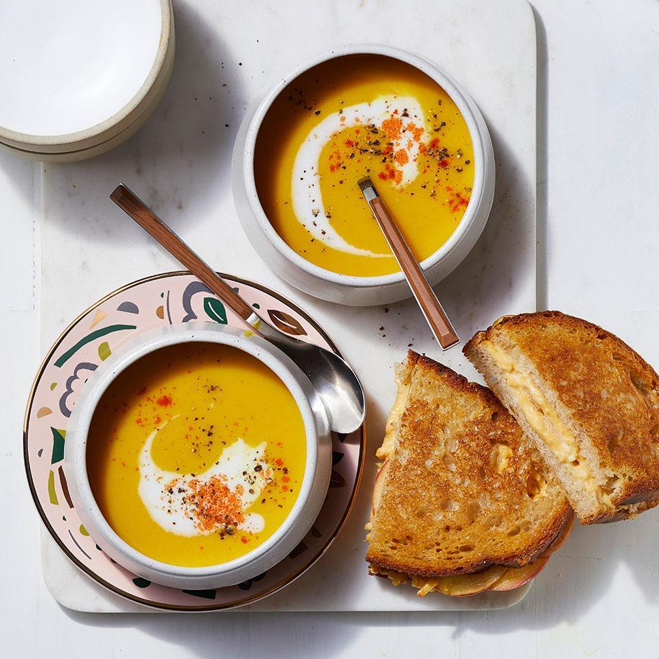 """<p>Layering apple slices into grilled cheese sandwiches adds a little crunch to a favorite soup dipper. And creamy butternut squash soup with ginger, cumin and turmeric is a nice change of pace from grilled cheese's usual tomato soup partner. Serve the duo for a comforting and easy weeknight dinner for the family. The soup keeps well in the fridge, so save leftovers for lunch or dinner later in the week. <a href=""""https://www.eatingwell.com/recipe/275766/butternut-squash-soup-with-apple-grilled-cheese-sandwiches/"""" rel=""""nofollow noopener"""" target=""""_blank"""" data-ylk=""""slk:View Recipe"""" class=""""link rapid-noclick-resp"""">View Recipe</a></p>"""