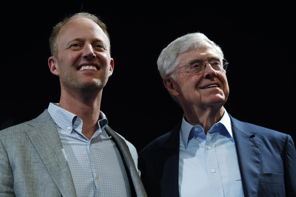 In this Saturday, June 29, 2019, file photograph, Charles Koch, chief executive officer of Koch Industries, right, is shown with his son, Chase Koch, at The Broadmoor Resort in Colorado Springs, Colo. (AP Photo/David Zalubowski)