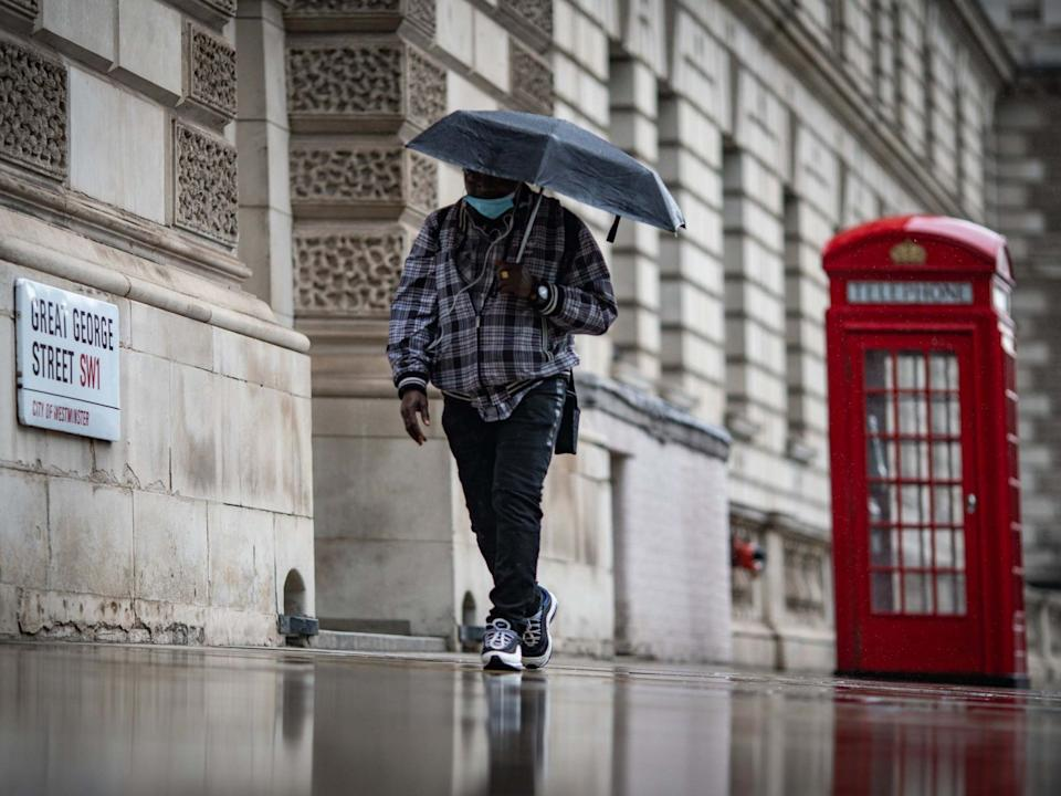 A man shelters from the rain under an umbrella in Westminster: PA