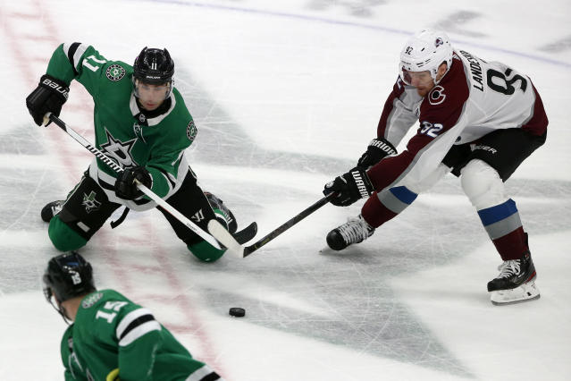 Dallas Stars center Andrew Cogliano (11) and Colorado Avalanche left wing Gabriel Landeskog (92) battle for the puck during the third period of an NHL hockey game in Dallas, Saturday, Dec. 28, 2019. (AP Photo/Michael Ainsworth)