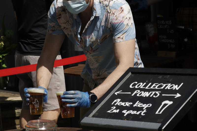 A member of staff wearing a face mask to protect from coronavirus places takeaway pints down on a collection point table for customers to then take, from the entrance of the Althorp pub, which is next to Wandsworth Common in south London, Tuesday, May 26, 2020. As part of the British government coronavirus lockdown pubs are not yet allowed to have customers drinking inside their premises, but are allowed to sell takeaway drinks. (AP Photo/Matt Dunham)