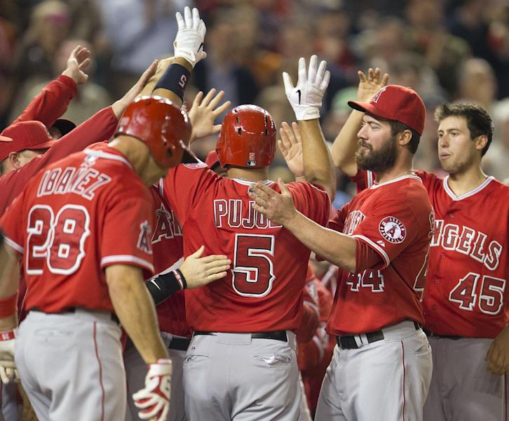 Los Angeles Angels Albert Pujols (5) is greeted his teammates at home plate after hitting a two-run homer against Washington Nationals Taylor Jordan in the fifth inning of a baseball game in Washington, Tuesday, April 22, 2014. This was Pujols 500th career home run. (AP Photo/Pablo Martinez Monsivais)