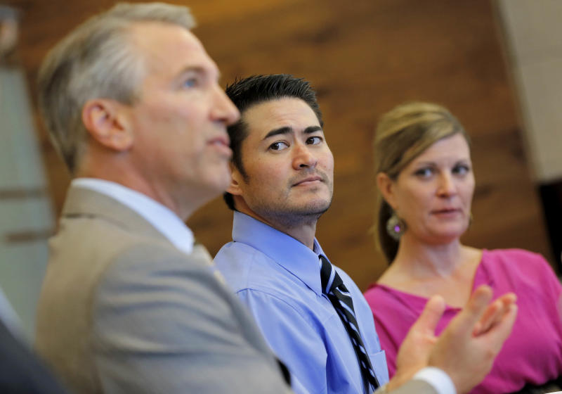 Thomas Beatie, center, and his girlfriend Amber Nicholas, listen as attorney David Michael Cantor speaks Tuesday, April 2, 2013, in Phoenix. Maricopa County Family Court Judge Douglas Gerlach ruled, March 29, 2013, that Arizona's ban on same-sex marriages prevents Thomas Beatie's 9-year union from being recognized as valid. Beatie was born a woman and later underwent a double-mastectomy, and began testosterone hormone therapy and psychological treatment to become a man, but he retained female reproductive organs and gave birth to three children. Gerlach said he had no jurisdiction to approve a divorce because there's insufficient evidence that Beatie was a man when he married Nancy Beatie in Hawaii. (AP Photo/Matt York)