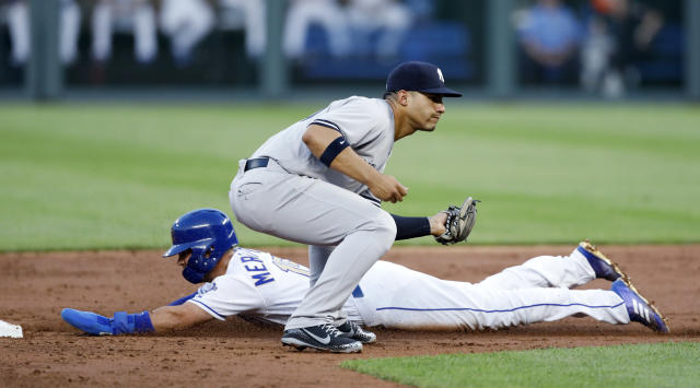 Kansas City Royals' Whit Merrifield, bottom, safely steals second base as New York Yankees second baseman Gleyber Torres, top, gets a late throw in the third inning of a baseball game at Kauffman Stadium in Kansas City, Mo., Friday, May 18, 2018. (AP Photo/Colin E. Braley)