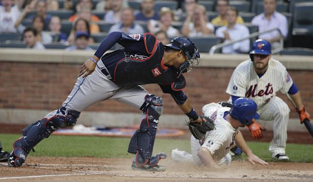 New York Mets second baseman Daniel Murphy (28) slides safely across home plate for a run ahead of the tag from Atlanta Braves catcher Christian Bethancourt (25) in the third inning of a baseball game, Tuesday, July 8, 2014, in New York. Murphy scored from second on a base hit by David Wright. (AP Photo/Julie Jacobson)