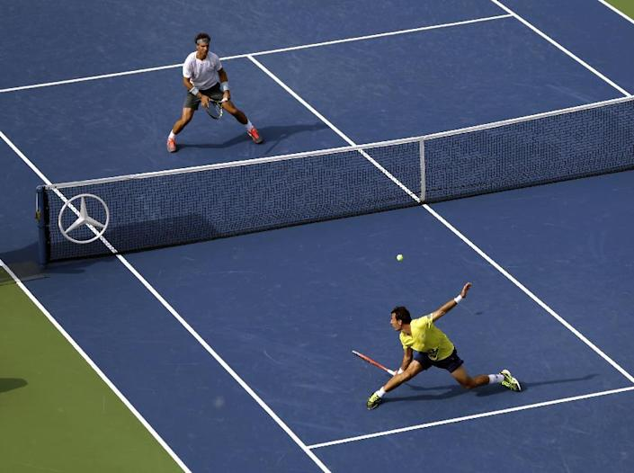 Ivan Dodig, of Croatia, bottom right, returns a shot to Rafael Nadal, of Spain, during the third round of the 2013 U.S. Open tennis tournament, Saturday, Aug. 31, 2013, in New York. (AP Photo/Mike Groll)