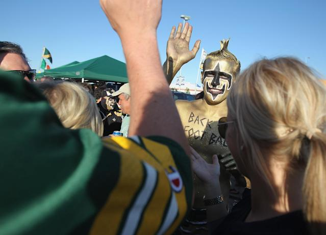 """GREEN BAY, WI - SEPTEMBER 08: A fan of the New Orleans Saints """"high fives"""" fans of the Green Bay Packers in the parking lot during the NFL opening season game at Lambeau Field on September 8, 2011 in Green Bay, Wisconsin. (Photo by Jonathan Daniel/Getty Images)"""