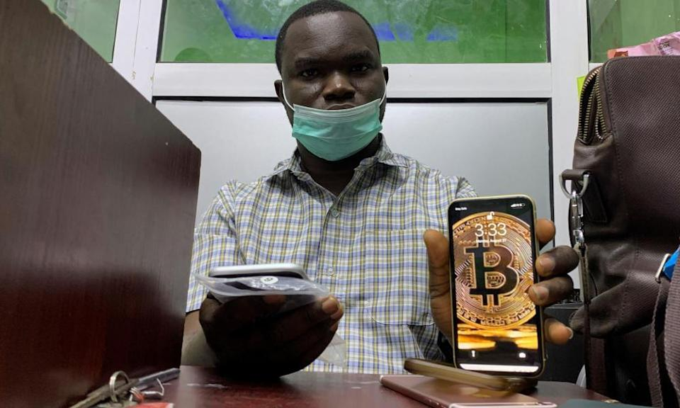 Abolaji Odunjo, a gadget vendor who uses bitcoin, poses with his mobile phone