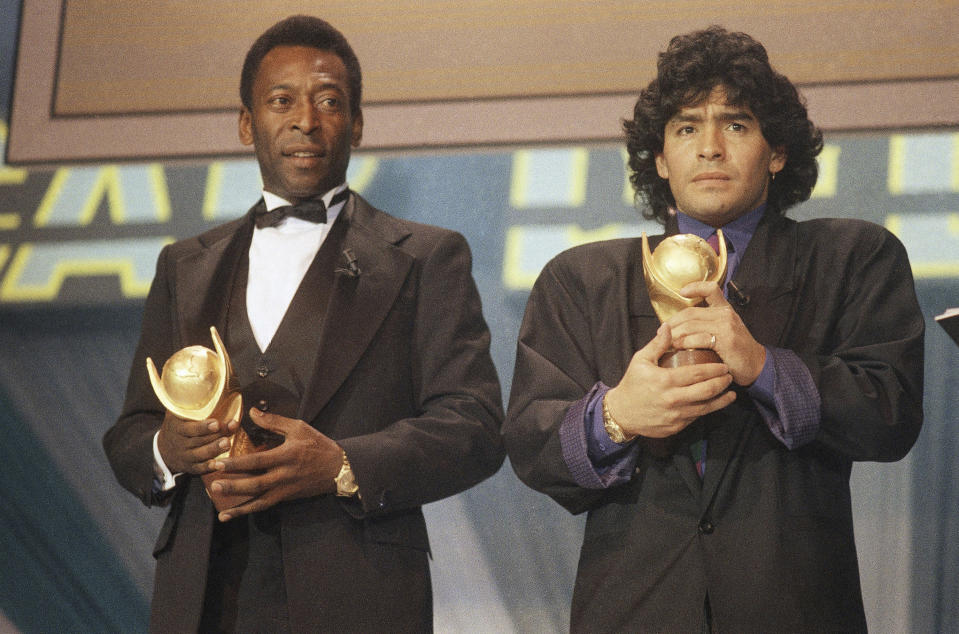 CORRECTS LOCATION - FILE - In this March 1987 file photo, Pele, left, and Diego Maradona, hold trophies during an awards ceremony in Italy. The Argentine soccer great who was among the best players ever and who led his country to the 1986 World Cup title before later struggling with cocaine use and obesity, died from a heart attack on Wednesday, Nov. 25, 2020, at his home in Buenos Aires. He was 60. (AP Photo/File)