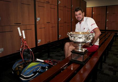 Stanislas Wawrinka of Switzerland sits with the Norman Brookes Challenge Cup in the locker room after defeating Rafael Nadal of Spain in their men's singles final match at the Australian Open 2014 tennis tournament in Melbourne