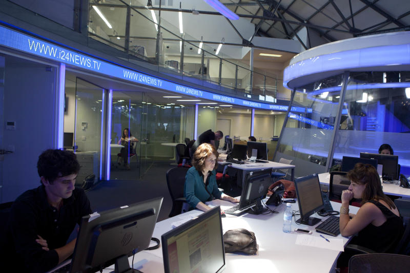 In this Sunday, July 28, 2013 photo, journalists work inside a studio of the new television channel I24news in Tel Aviv, Israel. The station's founders insist they are not an Israeli version of Al-Jazeera, the powerful broadcaster from the Gulf. They say they receive no government funding, hold no political affiliation and pledge to cover the news dispassionately and objectively. (AP Photo/Dan Balilty)