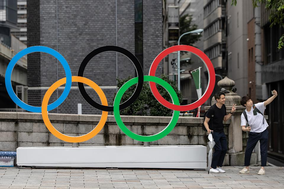 Two men take a selfie in front of the Olympic Rings in Tokyo, Japan.