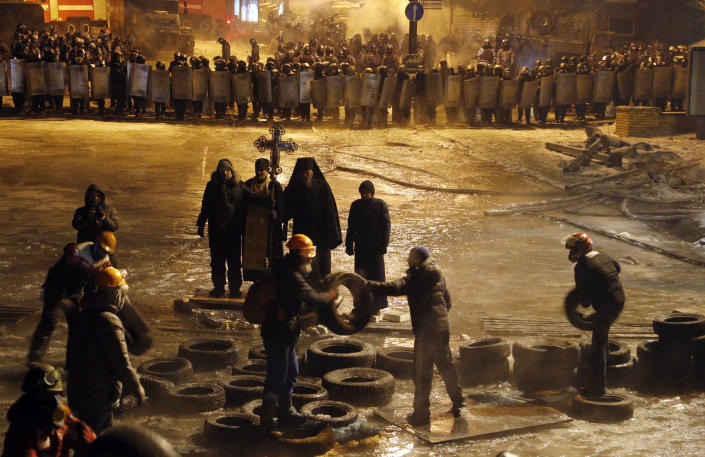 """Protesters clean tires from the street as Orthodox priests pray standing between pro-European Union activists and police lines in central Kiev, Ukraine, early Friday, Jan. 24, 2014. A top Ukrainian opposition leader on Thursday urged protesters to maintain a shaky cease-fire with police after at least two demonstrators were killed in clashes this week, but some in the crowd appeared defiant, jeering and chanting """"revolution"""" and """"shame."""" (AP Photo/Sergei Grits)"""