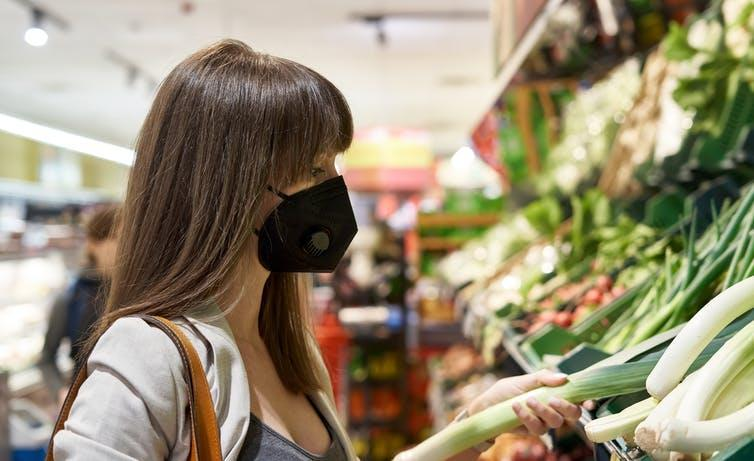 Woman with brown hair and black face mask picks up vegetable at supermarket