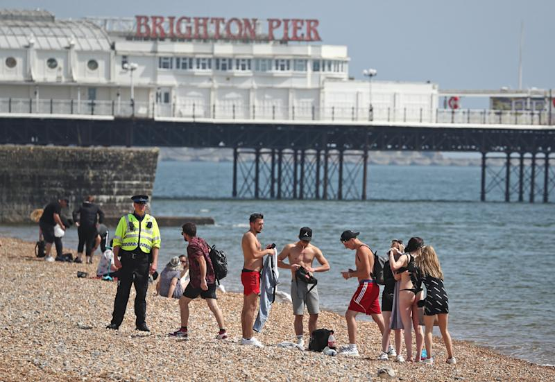 A police officer advises a group of people to move from Brighton Beach in East Sussex as the UK continues in lockdown to help curb the spread of the coronavirus. (Photo by Gareth Fuller/PA Images via Getty Images)