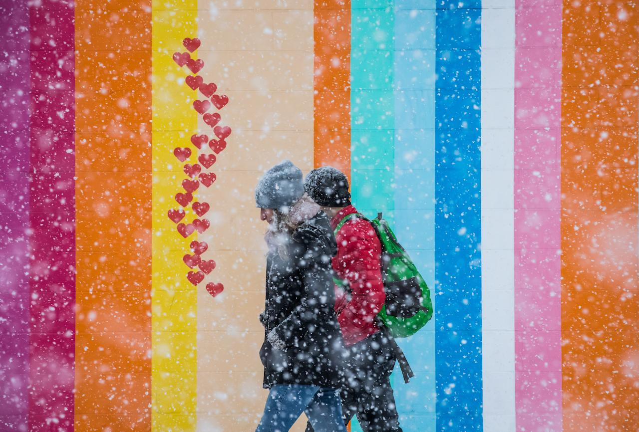 <p>Pedestrians walk past a wall painted with various colours as heavy snow falls in Vancouver, on February 10, 2019. THE CANADIAN PRESS/Darryl Dyck </p>