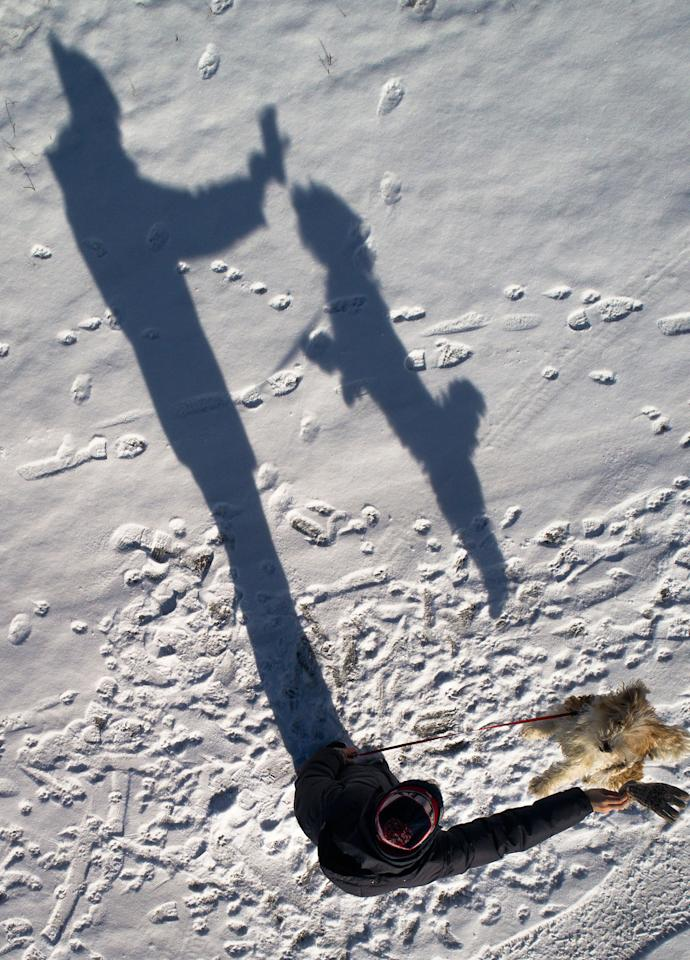 <p>A woman casts her shadow as she plays with her dog in St.Petersburg, Russia, Monday, March 6, 2017. (AP Photo/Dmitri Lovetsky) </p>