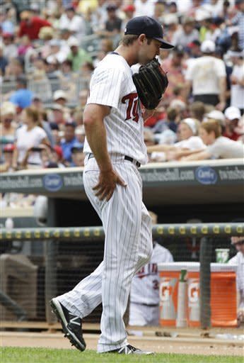 Minnesota Twins pitcher Casey Fien heads to the dugout at the end of the top half of the sixth inning of a baseball game against the Seattle Mariners, Thursday, Aug. 30, 2012, in Minneapolis. Fien gave up two runs in the inning. (AP Photo/Jim Mone)