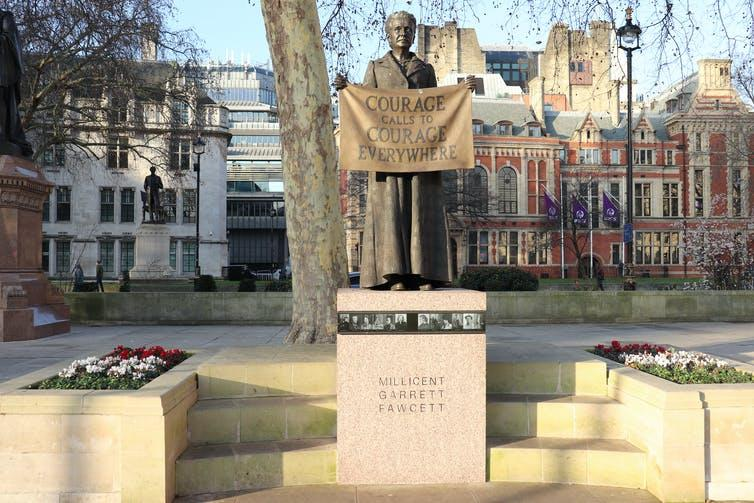 Statue of Millicent Fawcett holding a banner saying 'Courage calls to courage everywhere'