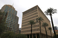 The Calvin C. Goode Municipal Building, right, stands adjacent to Phoenix City Hall, left, on Thursday, Dec. 24, 2020. The building was renamed after Goode when he retired from the City Council after 22 years, including two years as vice mayor. Phoenix city officials, residents and prominent members of the Black community will honor the late civil rights icon, city leader and longtime Arizona resident in the coming weeks. The events follow a public, open-casket viewing hosted on Saturday, Jan. 9, 2021, outside of the former city hall, renamed after Goode. (AP Photo/Cheyanne Mumphrey)