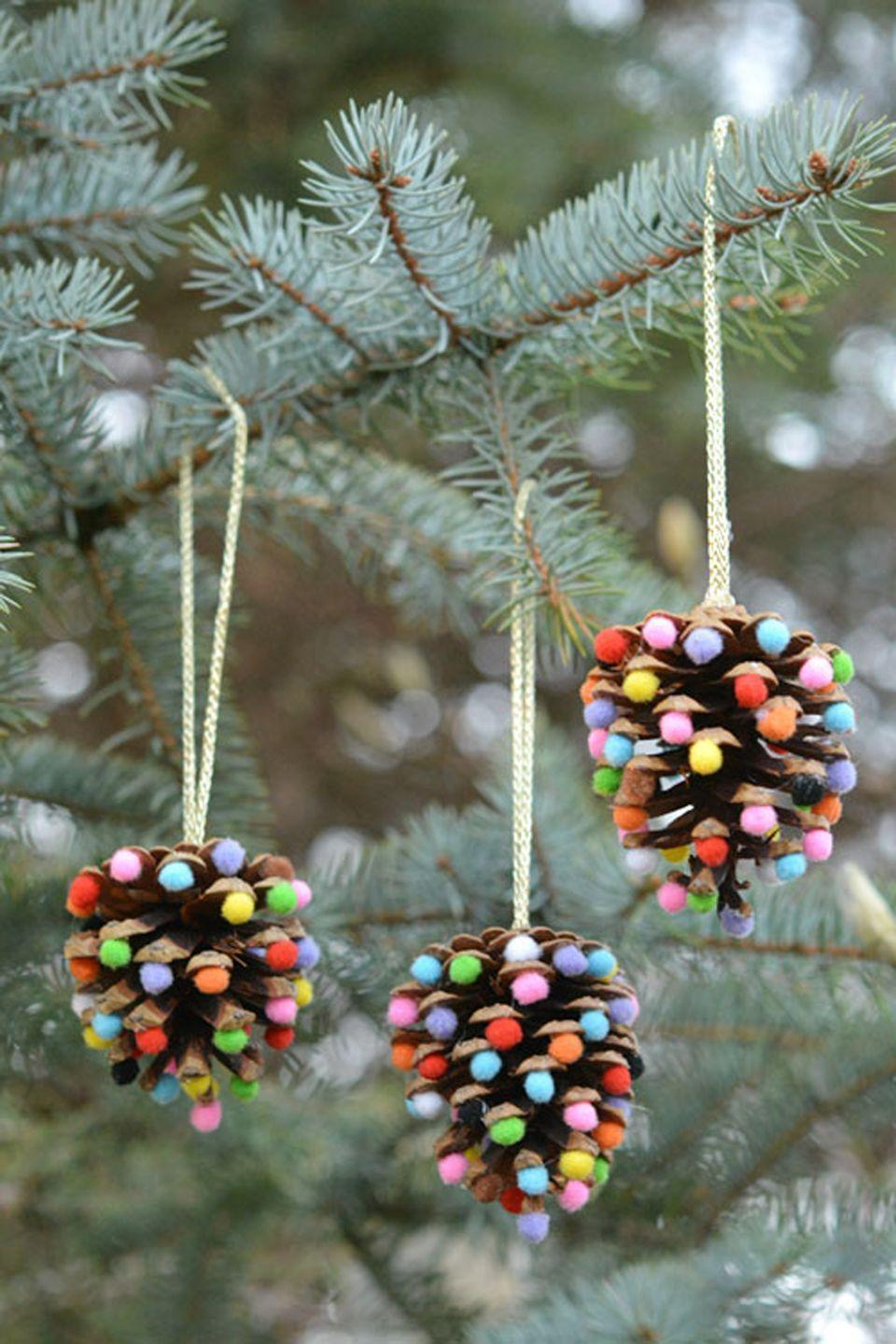 "<p>We're a fan of any craft that uses pom poms.</p><p><strong>Get the tutorial at <a href=""https://onelittleproject.com/pom-poms-and-pinecones-christmas-ornaments/"" rel=""nofollow noopener"" target=""_blank"" data-ylk=""slk:One Little Project"" class=""link rapid-noclick-resp"">One Little Project</a>.</strong></p>"