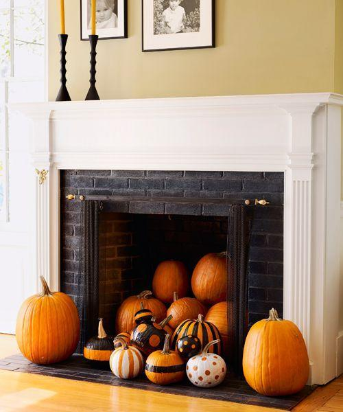 <p>Instead of the usual haunts, try grouping pumpkins in a less-expected locale, like an unused fireplace. For the these graphic gourds, use painter's tape and self-adhesive paper to mark off stripes and circles. Spray with glossy black and white paint, then casually pile in the hearth.</p>