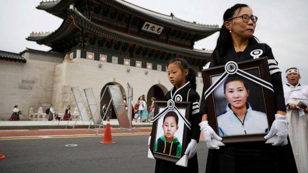 PHOTO: A girl and her North Korean defector mother hold portraits of a 42-year-old defector mother and her 6-year-old son who were found dead in starvation as they march during their funeral in Seoul, South Korea, Sept. 21, 2019. (Kim Hong-ji/Reuters)