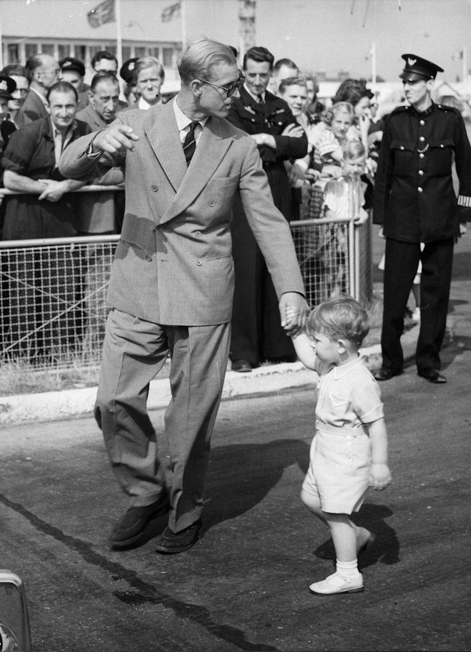 """<p>Prince Philip takes a young <a href=""""https://www.goodhousekeeping.com/uk/news/a25084414/young-prince-charles-queen-video-footage/"""" rel=""""nofollow noopener"""" target=""""_blank"""" data-ylk=""""slk:Prince Charles"""" class=""""link rapid-noclick-resp"""">Prince Charles</a> by the hand upon their arrival at London Airport from Malta, where the Duke relinquished command of the Royal Navy Frigate, HMS Magpie.</p>"""