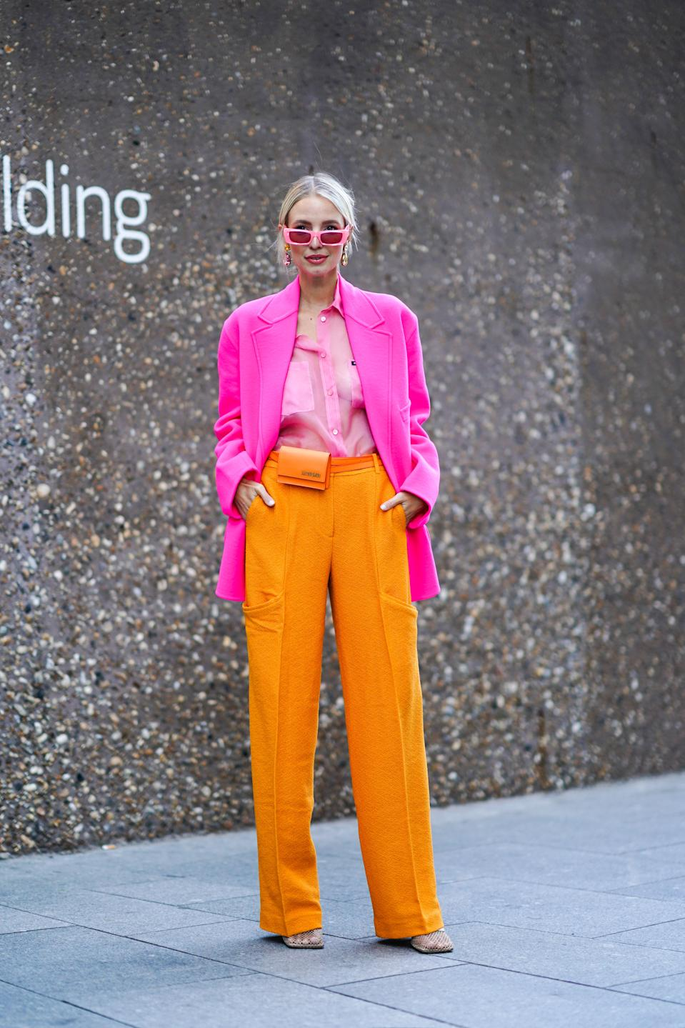 """Leonie Hanne is seen wearing a pair of pink sunglasses, earrings, a pink blazer jacket, a pink shirt, orange flare trousers and an orange Jacquemus belt bag. <a href=""""https://fave.co/31nhXgo"""" rel=""""nofollow noopener"""" target=""""_blank"""" data-ylk=""""slk:Shop the bag here"""" class=""""link rapid-noclick-resp"""">Shop the bag here</a>. [Photo: Getty Images]"""