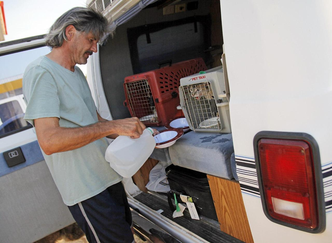 Vin Bayne pours water for his pets while waiting at a gas station at Hwy 9 and SE 108 Ave. after evacuating his home as a wildfire burns through Cleveland County near Norman, Okla., Friday, Aug. 3, 2012. A wildfire stirred by high winds sweeping through rural woodlands just south of the Oklahoma City area has set at a number of homes on fire. (AP Photo/The Oklahoman, Nate Billings) TABLOIDS OUT