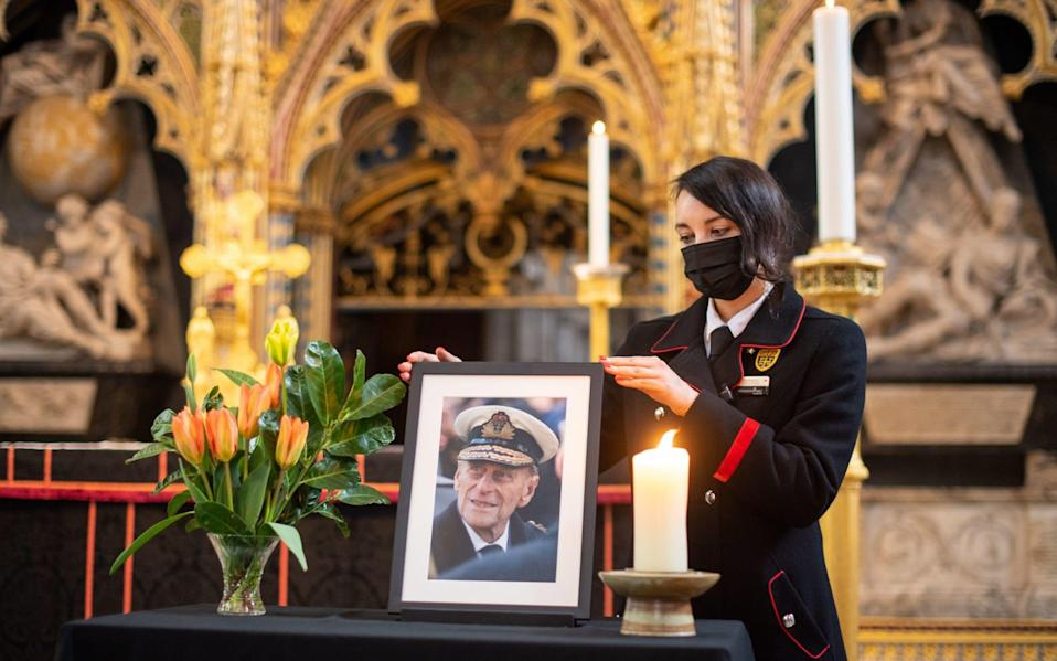 Rosa Wlodarczyk adjusts a photograph of the Duke of Edinburgh displayed alongside the nave at Westminster Abbey, London, which has been dressed in black to mark his death - Dominic Lipinski/PA