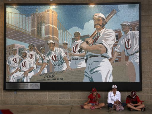 Shannon Nelson, middle, sits under a mural with her daughter Kerrington Nelson, left, and son Brookes Nelson, right, waiting during a rain delay before a Cincinnati Reds baseball game with the San Francisco Giants, Sunday, May 12, 2013, in Cincinnati. The game was postponed. (AP Photo/David Kohl)