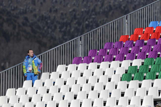 A volunteer stands in an empty grandstand during the women's snowboard slopestyle qualifying at the Rosa Khutor Extreme Park ahead of the 2014 Winter Olympics, Thursday, Feb. 6, 2014, in Krasnaya Polyana, Russia. (AP Photo/Andy Wong)