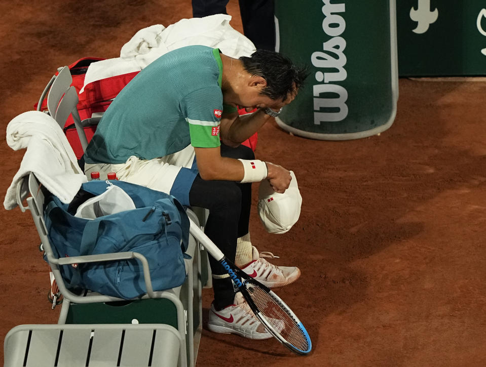 Japan's Kei Nishikori sits in his chair and looks down during a change of ends as he plays against Germany's Alexander Zverev during their fourth round match on day 8, of the French Open tennis tournament at Roland Garros in Paris, France, Sunday, June 6, 2021. (AP Photo/Michel Euler)