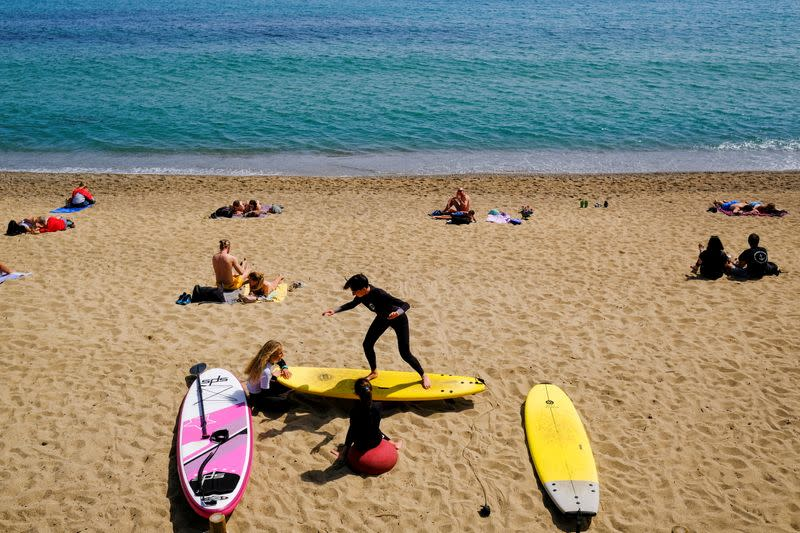 FILE PHOTO: A person teaches surfing to children at Barceloneta beach, in Barcelona