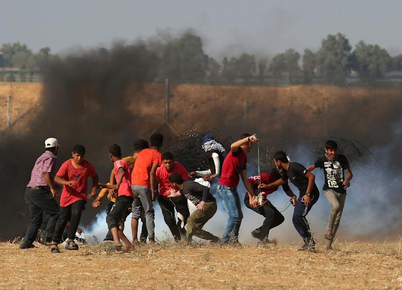 Palestinian protesters flee tear gas canisters fired by Israeli soldiers along the border with Israel near Khan Yunis in the southern Gaza Strip