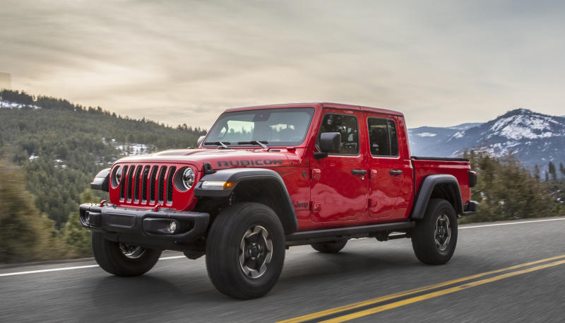 A red 2020 Jeep Gladiator Rubicon, a Jeep-Wrangler-based pickup, on a mountain road