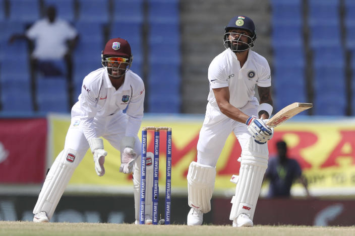India's captain Virat Kohli eyes the ball after playing a shot to be caught by West Indies' John Campbell during day four of the first Test cricket match at the Sir Vivian Richards cricket ground in North Sound, Antigua and Barbuda, Sunday, Aug. 25, 2019. (AP Photo/Ricardo Mazalan)