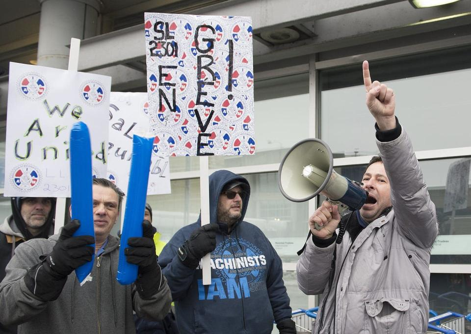 Striking workers hold signs as one speaks into a megaphone.