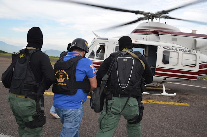 """In this photo provided by the Ministry of Popular Power for Interior Relations and Justice, Venezuela's judicial police officers escort alleged Colombian drug trafficker Daniel Barrera, center, toward a helicopter at the Regional Command No. 1 National Guard base in San Cristobal, Tachira state, Venezuela, Wednesday, Sept. 19, 2012. Colombia's President Juan Manuel Santos announced Tuesday evening that a man he described as Colombia's last big-time drug lord had been captured in neighboring Venezuela. It was the third arrest of a purported Colombian drug boss in the last year. Santos said alleged drug boss Daniel """"Loco"""" Barrera was arrested in the Venezuelan city of San Cristobal after months of multinational cooperation that included help from the U.S. and other nations. (AP Photo/Ministry of Popular Power for Interior Relations and Justice)"""