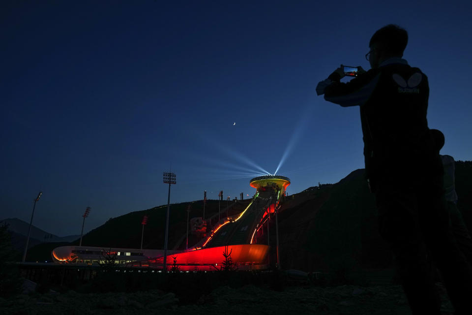 FILE - In this July 14, 2021, file photo, a reporter uses his smartphone to film a light show at the National Ski Jumping Centre, one of the venues for Beijing 2022 Olympic and Paralympic Winter Games, during a media tour in Zhangjiakou in northwestern China's Hebei province. When the International Olympic Committee awarded Beijing the 2008 Summer Olympics, it promised the Games could improve human rights and civil liberties in China. (AP Photo/Andy Wong, File)
