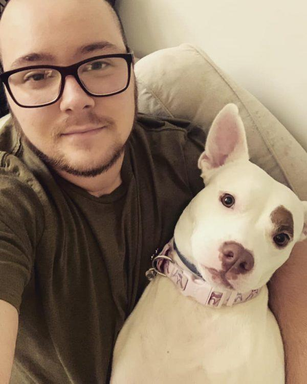 A person holds his dog on a couch