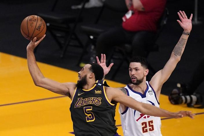 Los Angeles Lakers guard Talen Horton-Tucker, left, shoots as Denver Nuggets guard Austin Rivers defends during the second half of an NBA basketball game Monday, May 3, 2021, in Los Angeles. (AP Photo/Mark J. Terrill)
