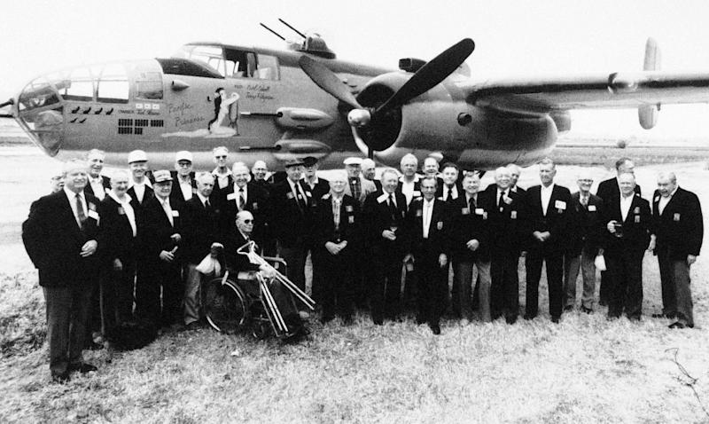 FILE - In this April 17, 1987 file photo, thirty members of Jimmy Doolittle's Tokyo Raiders pose for a group picture in front of a B-25J bomber in Torrance, Calif., as they gather for a reunion. Thousands of visitors streamed to the national Air Force museum on Saturday, Nov. 9, 2013 to pay a Veterans Day weekend tribute to the few surviving members of the Doolittle Raiders, airmen whose daring raid on Japan helped boost American morale during World War II, as they planned to make their ceremonial final toast together. Only four of the 80 Raiders are still living, and one was unable to attend because of health issues. (AP Photo/Douglas C. Pizac)